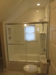 After - New shower area, Brick subway tile, new tub with glass shower doors